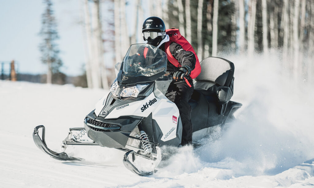 man wearing a red jacket and riding a snowmobile